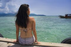 Young Asian woman sitting happy on sea dock at Thailand beach looking at the horizon beautiful marine landscape with mountains enj. Oying holiday relaxed in Stock Photography