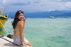 Young Asian woman sitting happy on sea dock at Thailand beach looking at the horizon beautiful marine landscape with mountains enj. Oying holiday relaxed in Royalty Free Stock Photos