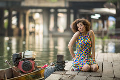 Young  asian woman sitting on a river dock. Stock Photos