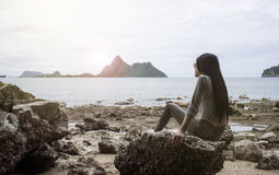Young asian woman sitting on a rock near the sea,looked to the sea,chill out of summer,rest time,light and flare effect added. Wait for somthing concept Stock Images