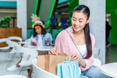 Young asian woman sitting with shopping bags in shopping mall Stock Photos