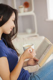 Young asian woman sitting on the sofa reading a book holding her Royalty Free Stock Photo