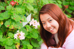 Young asian woman smile in garden. Young asian woman smile in front of hydrangea flowers Royalty Free Stock Image