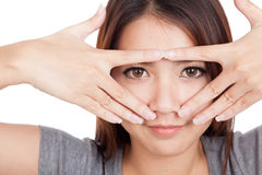 Young Asian woman smile peeking though her fingers Royalty Free Stock Image