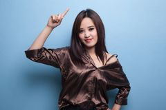 Young Asian woman smile and point up. Royalty Free Stock Images