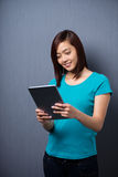 Young Asian woman smiling as she reads a tablet. Pretty young Asian woman smiling as she stands reading a tablet computer in front of a dark studio background Royalty Free Stock Images