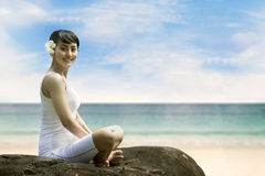 Young Asian Woman Smiling at Beach. Beautiful Asian Woman in Yoga position smiling at beach Royalty Free Stock Images
