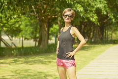 Young Asian woman smiling at camera after jogging in  park Royalty Free Stock Image