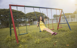 Young asian woman smiling happy and enjoy to play a swings at a playground,selective focus,filtered image,light and flare effect royalty free stock images