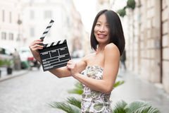 Young asian woman smiling showing clapper board Royalty Free Stock Photography