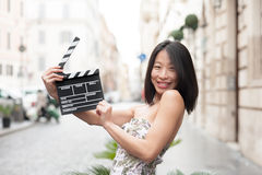 Young asian woman smiling and shows clapperboard urban scene Royalty Free Stock Image