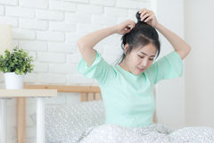 Young Asian woman smiling while sitting on bed. Young attractive Asian woman wear green casual cloth smiling while sitting on bed. Lazy girl activity on sunday Stock Photo