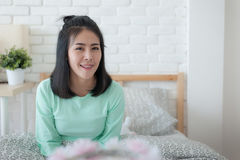 Young Asian woman smiling while sitting on bed. Young attractive Asian woman wear green casual cloth smiling while sitting on bed. Lazy girl activity on sunday Stock Images