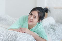 Young Asian woman smiling while sitting on bed. Young attractive Asian woman wear green casual cloth smiling while laying down on bed. Lazy girl activity on Stock Photos