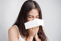 Young Asian woman sneezing, catch a cold. Royalty Free Stock Photo