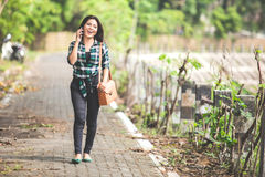 Young asian woman speaking on the phone while walking on the par Royalty Free Stock Photography