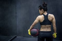 Young Asian woman in sportwear holding basketball Royalty Free Stock Photo