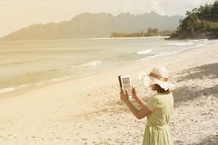 Young Asian woman standing and taking a photo on the beach. Young pretty Asian woman standing on the beautiful nice blue beach with taking a photo by tablet Royalty Free Stock Photo