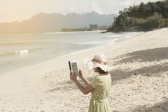 Young Asian woman standing and taking a photo on the beach. Young pretty Asian woman standing on the beautiful nice blue beach with taking a photo by tablet Stock Photography
