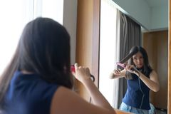 Young Asian woman straightening hair with hair straightener whil Royalty Free Stock Photo