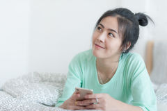 Young Asian woman stretching on bed after wake up. Young attractive Asian woman wear green casual cloths stretching after wake up on bed. Lazy girl activity on Royalty Free Stock Photo