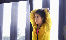 Young asian woman stretching her arm and shoulder Stock Image