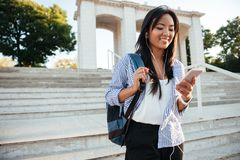 Young asian woman in striped shirt checking her phone, while goi. Ng down stairs Stock Image