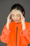 Young Asian woman suffering from headache in prisoners uniform Royalty Free Stock Photo