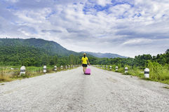 Young asian woman with suitcase walking alone and mountain blue. Sky background on the road Stock Photos