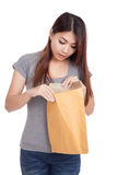 Young Asian woman surprise look inside brown envelope Royalty Free Stock Images