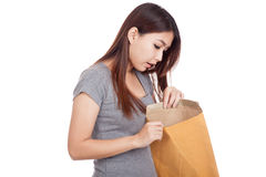 Young Asian woman surprise look inside brown envelope Royalty Free Stock Photo