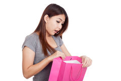 Young Asian woman surprise look inside shopping bag Stock Photography