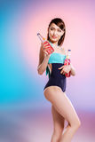 Young asian woman in swimsuit holding bottles with refreshing summer drinks and looking away Stock Photography
