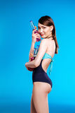 Young asian woman in swimsuit holding bottles with refreshing summer drinks and looking at camera Royalty Free Stock Photo