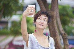 Young asian woman taking photo of herself in plaza Stock Images