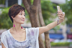Young asian woman taking photo of herself in plaza Stock Photography