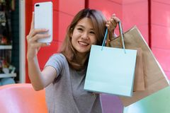 Young Asian woman taking selfie of herself with shopping bags after shopping in outdoor mall. Young woman and her city lifestyle on the weekend`s morning. City Royalty Free Stock Photo