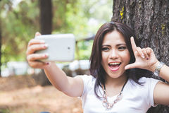 Young asian woman taking a selfie while sitting outdoor in a par Royalty Free Stock Photography