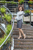 Young asian woman talking on mobile standing on the steps. Royalty Free Stock Photos