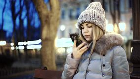 Young Asian woman talking on smart phone, sitting on a wooden bench in the park of the city at night stock footage