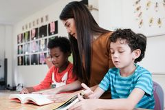 Young asian woman teacher and American, African boys in kindergarten classroom, preschool education concept. Young asian women teacher and American, African boys stock photography