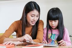 Young asian woman teacher teaching girl in kindergarten classroom, preschool education concept. Young asian women teacher teaching girl in kindergarten classroom stock photo