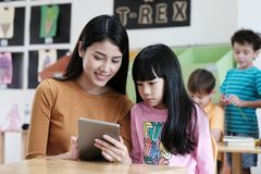 Young asian woman teacher teching girl by using tablet, education online, technology lifestyle. Young asian women teacher teching girl by using tablet, education stock images