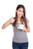 Young Asian woman thumbs up with cup of coffee Stock Photos
