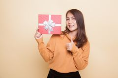 Young Asian woman thumbs up with a gift box. Young Asian woman thumbs up with a gift box on beige background Stock Image