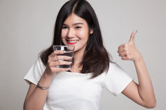 Young Asian woman thumbs up with a glass of drinking water. Young Asian woman thumbs up with a glass of drinking water on gray background Stock Images