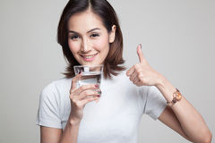 Young Asian woman thumbs up with a glass of drinking water. Young Asian woman thumbs up with a glass of drinking water on gray background Stock Photos
