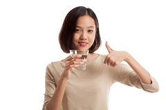Young Asian woman thumbs up with a glass of drinking water Royalty Free Stock Images