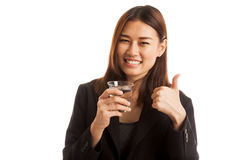 Young Asian woman thumbs up with a glass of drinking water. Royalty Free Stock Photography