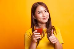 Young Asian woman thumbs up with tomato juice in yellow dress. On yellow background Royalty Free Stock Images